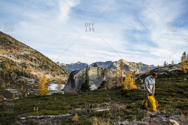 A backpacker unpacks by the Cascades in the Pasayten Wilderness on the Pacific Crest Trail in Washington