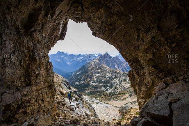 A climber stands at the mouth of a cave in the Pasayten Wilderness and the North Cascades of Washington at sunset