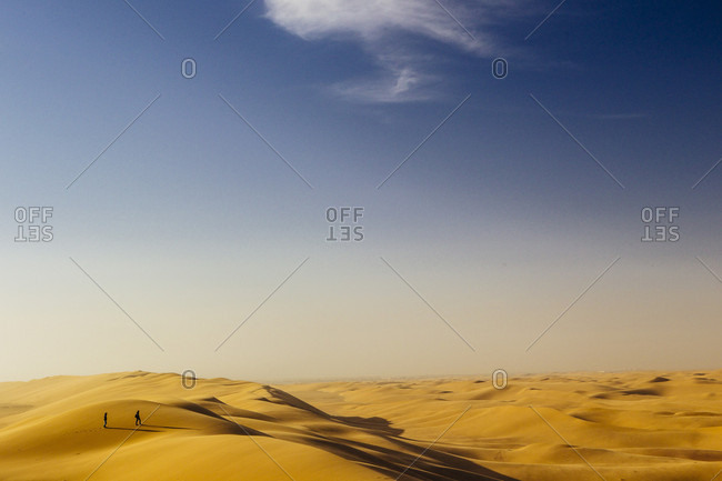 Two persons stand on the top of the highest dunes in Namibia
