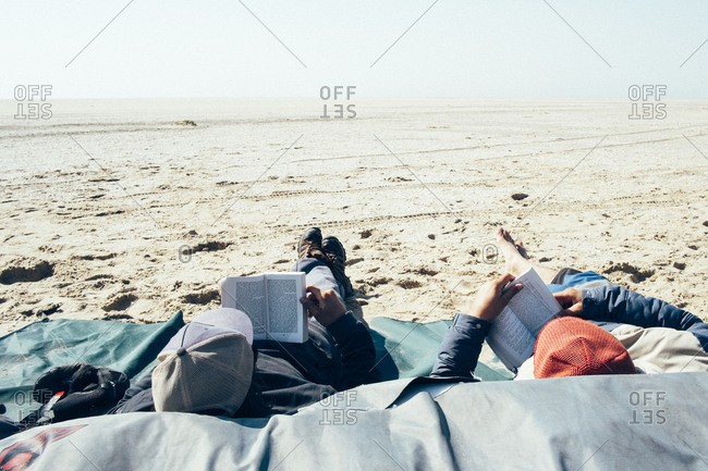 Two boys read a book while chilling on the beach