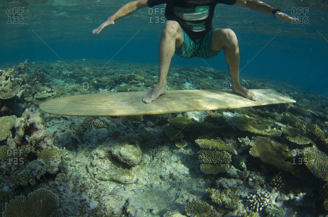 A boy stands on a submerged alaia in the Maldives