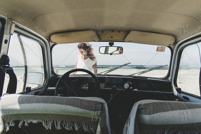 Girl through the windshield glass of her vintage car