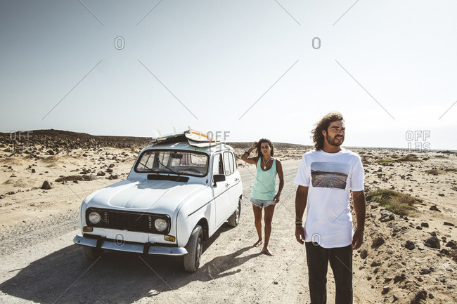 Body and girl drive a vintage car searching for waves