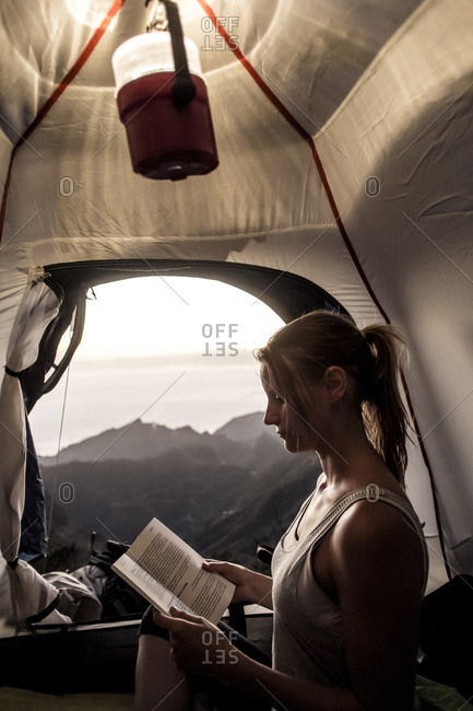 A female camper reads a book under the light of a lamp inside her tent