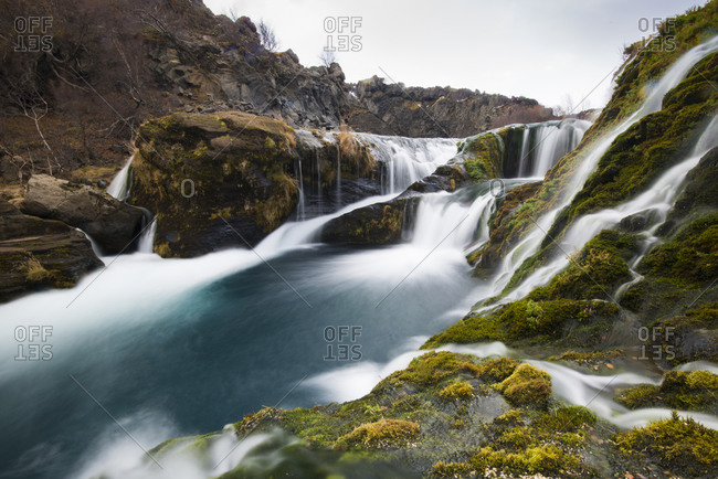 A long-exposure of a set of waterfalls falling down through a volcanic valley in Iceland