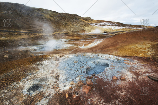 A geothermal pool steams amongst an explosion of earthen colors in Iceland