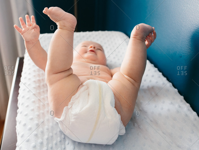 ... Baby in a diaper lying on its back on a changing table