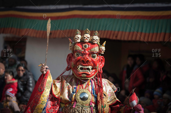 A person dressed in costume holding a scepter during a cham dance