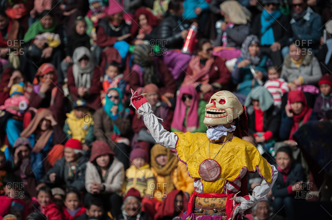 A person in a skull mask during a cham dance