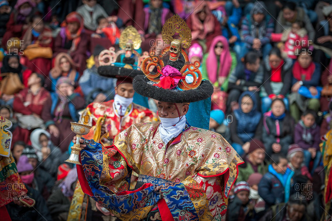 Leh, India - January 7, 2016: Men in costume holding chalices during a cham dance