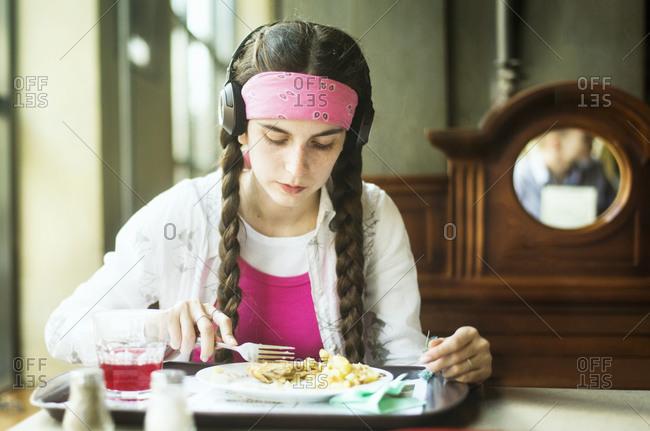 Woman wearing headphones eating in dining room