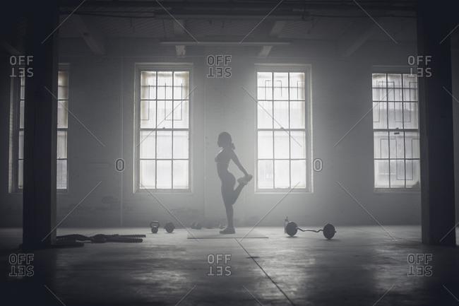 Woman stretching in dark gym