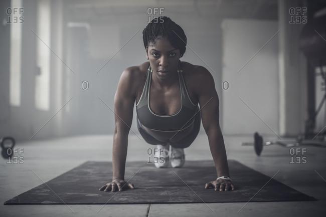 Woman doing push-ups in dark gym