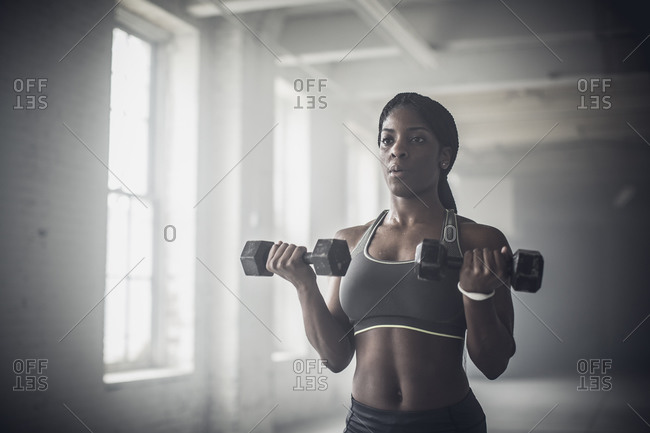 Woman lifting weights in dark gym