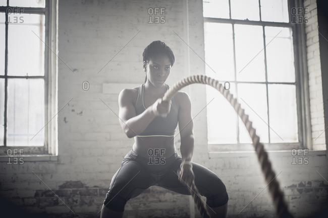 Woman tossing ropes in dark gym