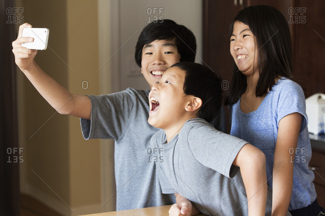 Asian brothers and sister taking cell phone photograph