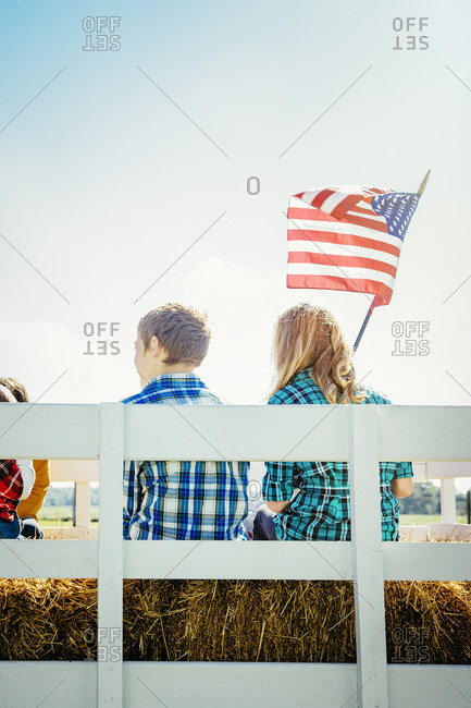 Children waving American flag on hay ride