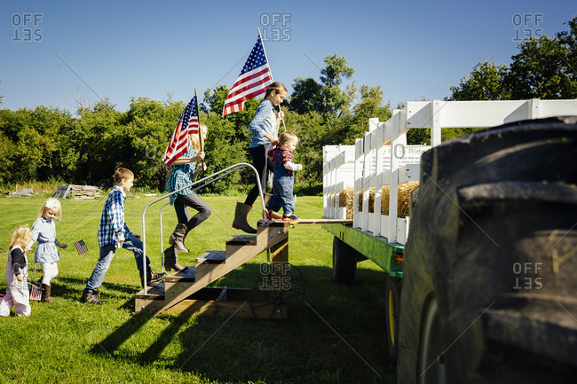 Children climbing stairs to hay ride on farm