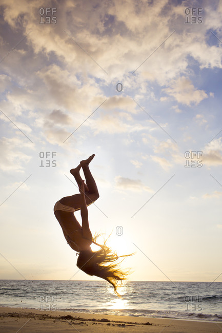 Silhouette of mixed race woman doing backflip on beach