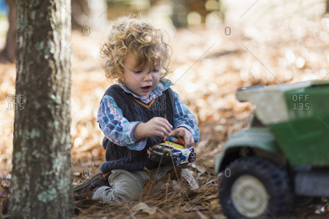 Boy playing with toy trucks in forest