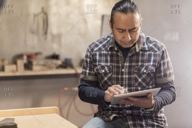 Native American artist using digital tablet in studio