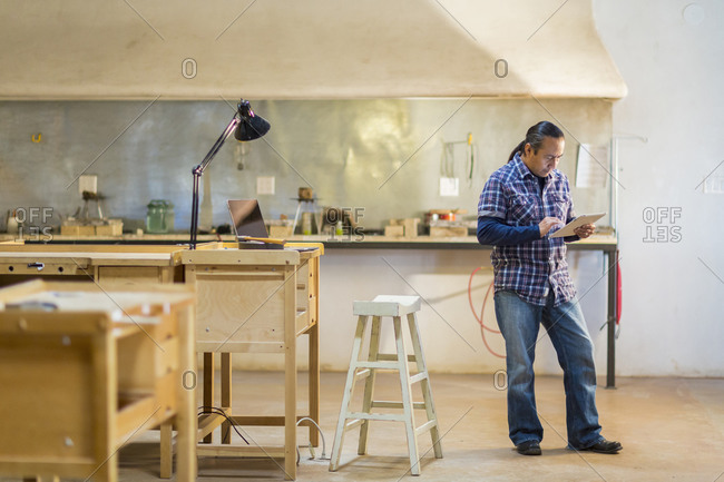 Native American artist using digital tablet in studio