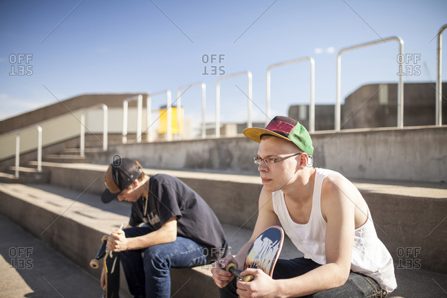 Young men with skateboards sitting on steps