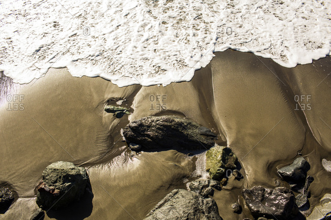 Ocean waves washing up on rocky beach