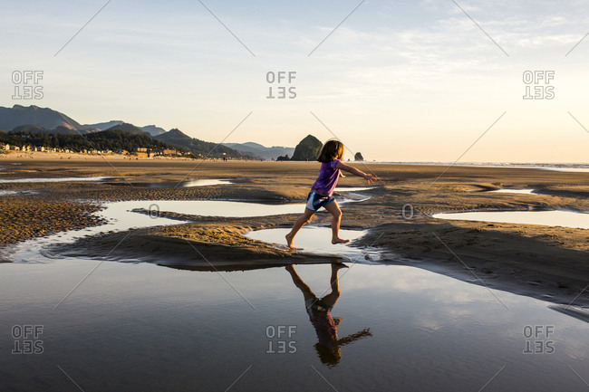 Girl running in tide pools on beach, Cannon Beach