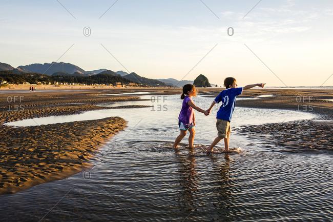 Caucasian children walking in tide pools on beach, Cannon Beach