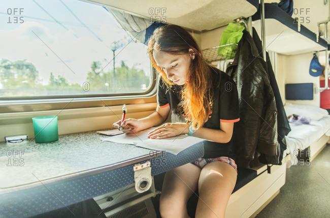 Girl writing on train