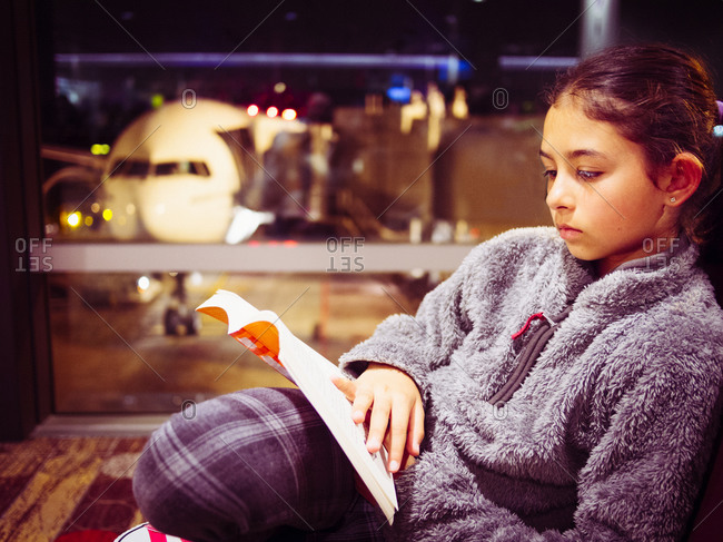 Girl reading book in airport
