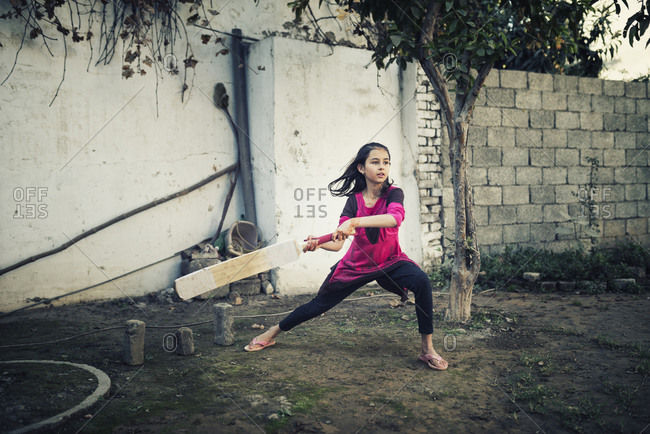 Girl playing cricket near wall