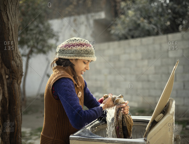 Young woman in knit hat hand-washing clothing outdoors