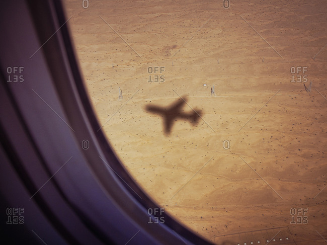 Shadow of airplane on desert ground