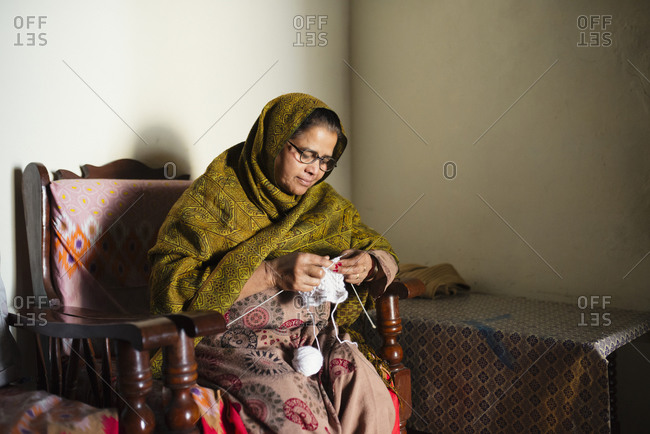 Elderly woman knitting baby clothes