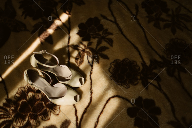 White peep-toe shoes on a floral rug