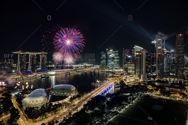 Fireworks bursting over the Singapore skyline at night