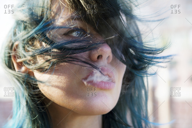 Young woman with blue hair exhaling smoke