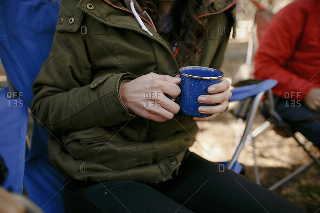 Woman in camping chair with metal mug