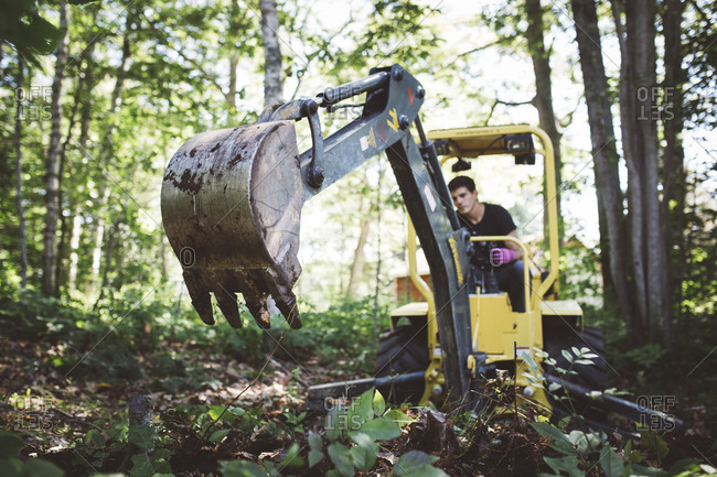 A man using digging machine in woods