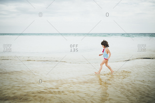 A girl strolling in the surf