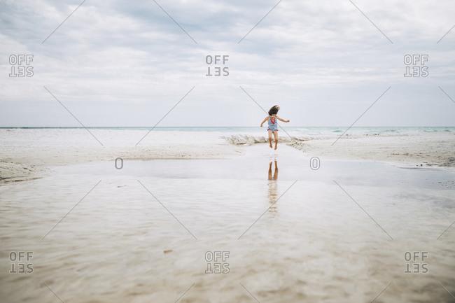 Girl in midair leap on beach