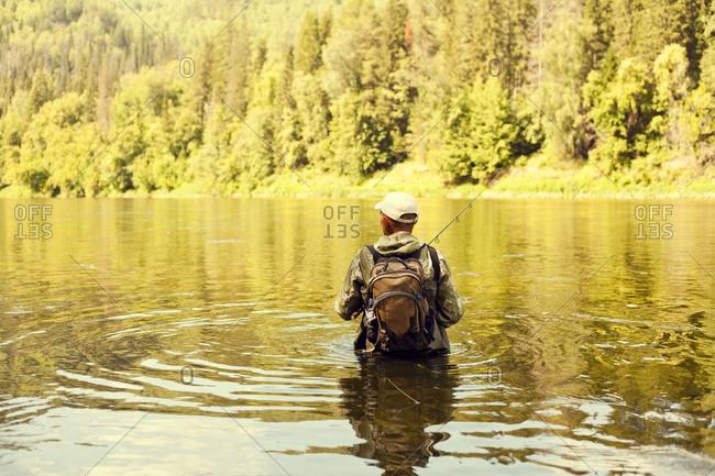 Fisherman holding fishing rod in lake