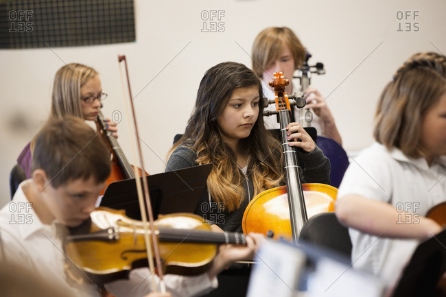 Students playing string instruments in music class