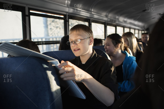 Young boy reading on school bus