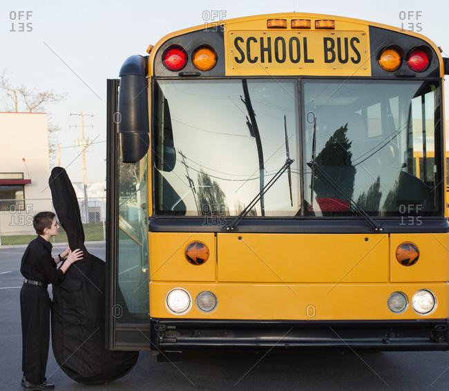Boy carrying bass onto school bus