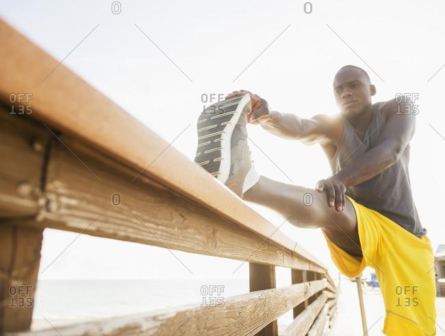 Runner stretching leg on banister