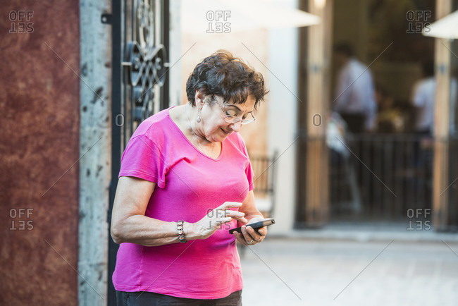 Older woman using cell phone in city
