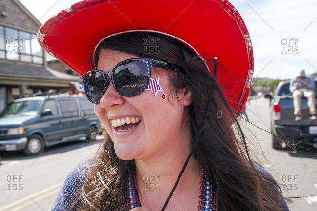 Woman wearing cowboy hat and face paint in street